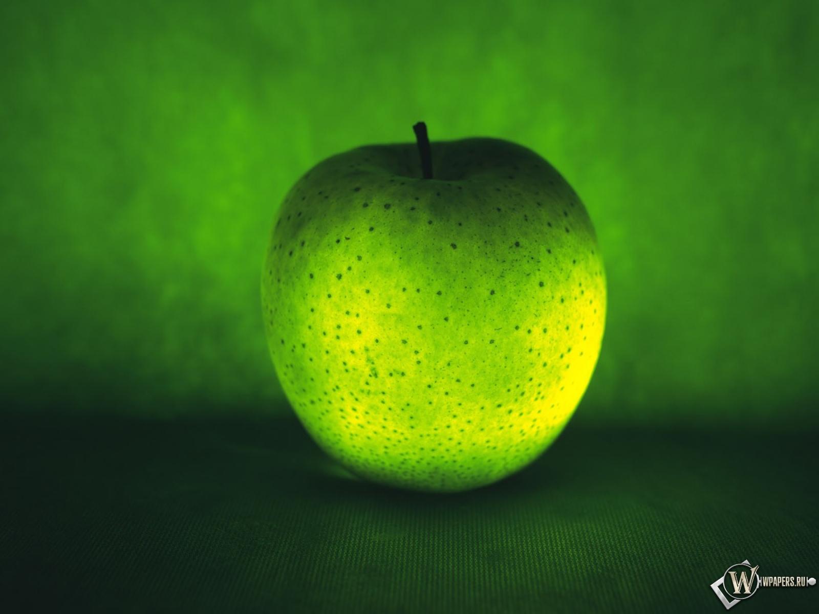 Зеленое яблоко на зеленом фоне