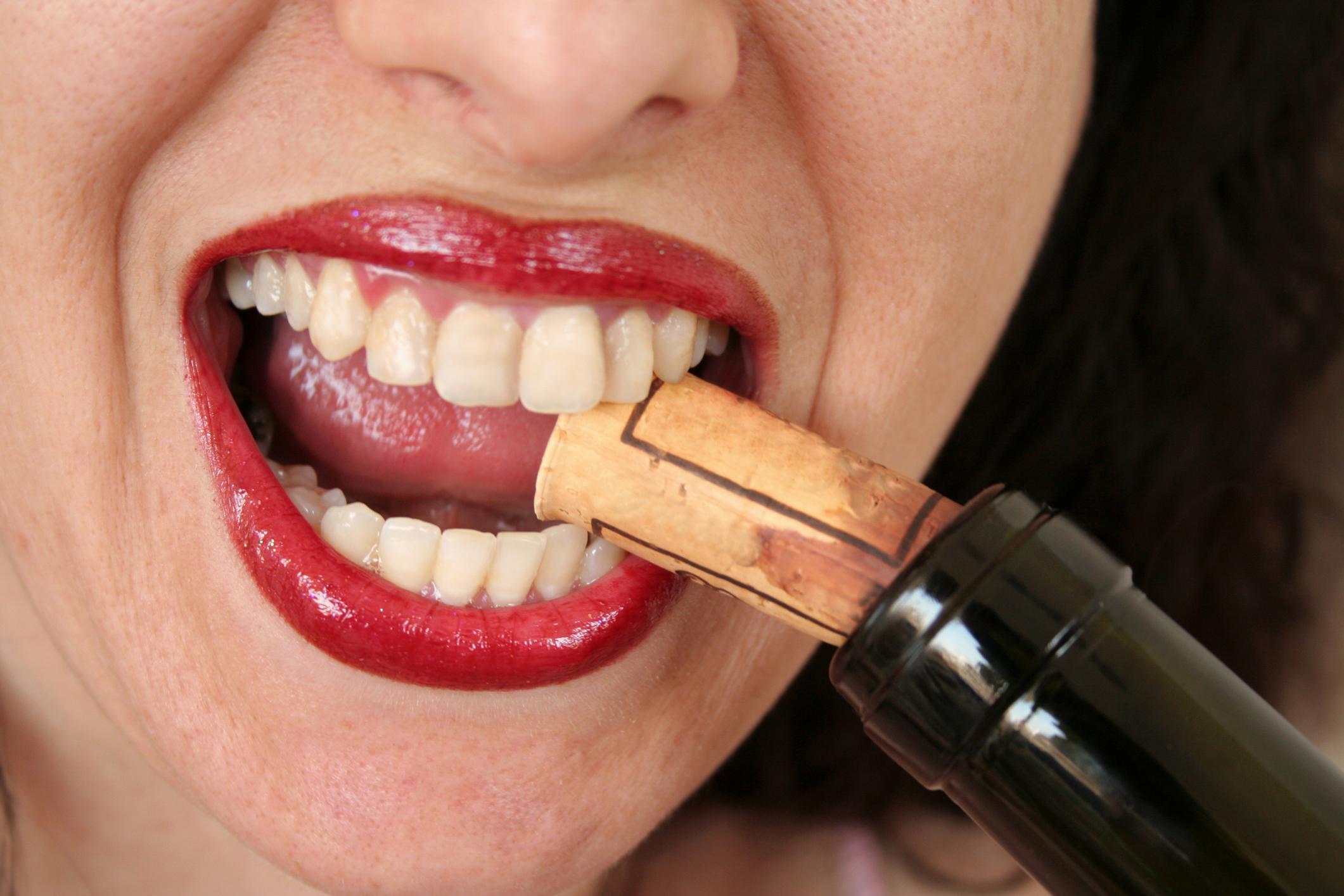 девушка открывает зубами пробку вина, скачать фото