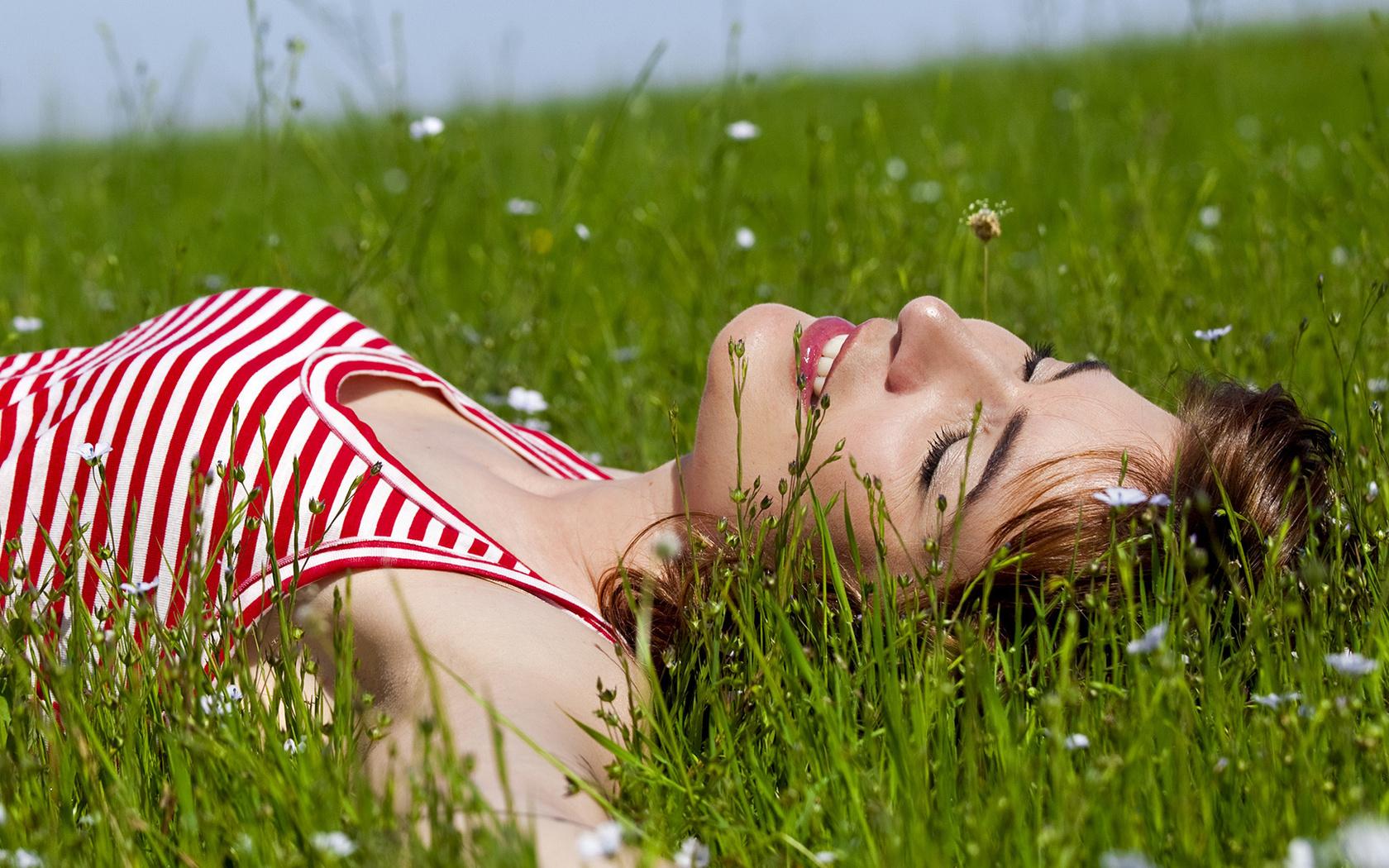 девушка лежит на зеленой поляне среди ромашек, скачать фото