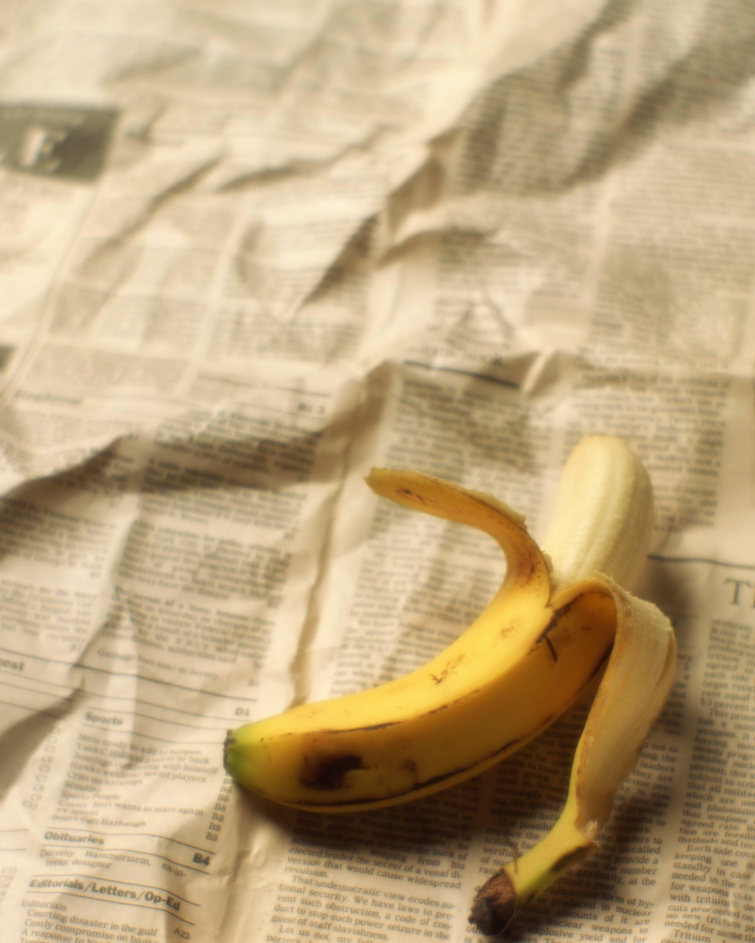 очищенный банан лежит на газете, скачать фото, обои для рабочего стола